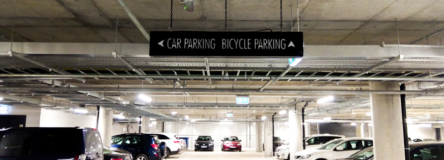 A double-sided fret-cut lightbox steers drivers around this busy office car park